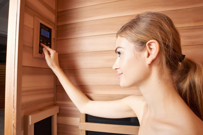 Woman using touch panel in low EMF sauna