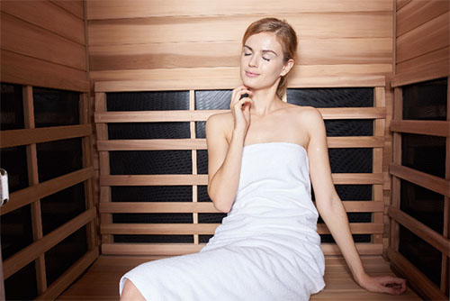 Woman using an infrared sauna for detoxification