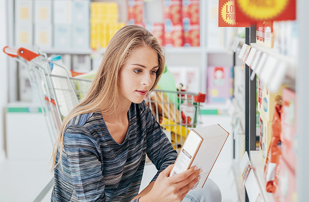 Woman Reading Nutritional Information on Natural Food Box